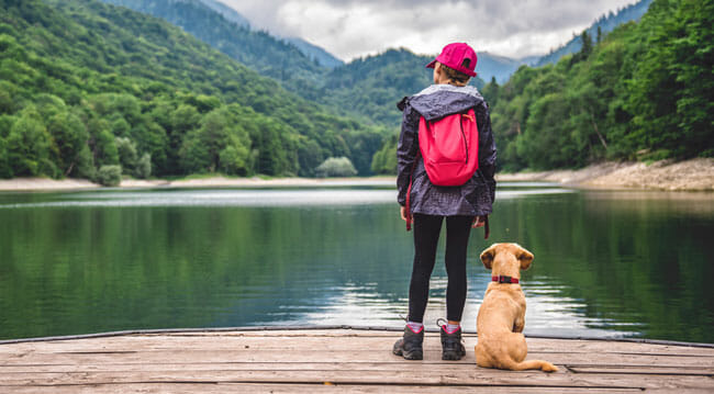 Girl with a small yellow dog standing on pier by the mountain lake